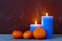 Candles And Oranges. Still life with two blue burning candles and three oranges on old grungy background royalty free stock photo