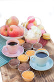 Still life of two coffee cups, cup-cakes, and apples Stock Photo