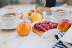Still life with two cups of tea in a vintage cups and  two tarts with fresh fruits on a white vintage background Royalty Free Stock Image