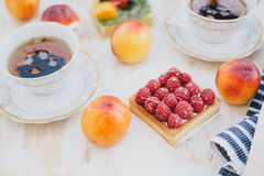 Still life with two cups of tea in a vintage cups and  two tarts with fresh fruits on a white vintage background Stock Photography