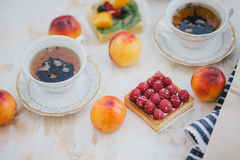 Still life with two cups of tea in a vintage cups and  two tarts with fresh fruits on a white vintage background. Still life with two cups of tea in a vintage Stock Photography