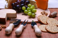 Still life 3 types of cheese roquefort cheese, red and green grapes, crackers, walnuts, cheese utensils on wooden plate. Still life 3 types of cheese, red and Royalty Free Stock Images