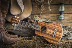 Still life with ukulele on cowboy hat and traditional leather bo Stock Photos