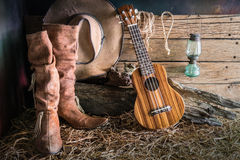 Still life with ukulele on cowboy hat and traditional leather bo Royalty Free Stock Images