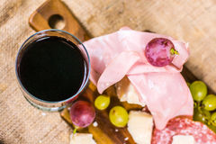 Still life - upper shot of yellow and red muscat grape, cheese, salami and a glass of red wine on a wooden board and canvas Royalty Free Stock Photography