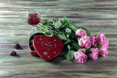 Wine in a glass, roses and a box of chocolates on a wooden table Stock Photography