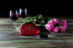 Wine in glasses, roses and a box of sweets on a wooden table Stock Photos