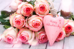Still life for Valentines Day. With a rose bouquet and a pink heart on a wooden table Stock Photos