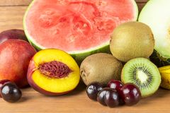 Still life with varied fruits on wooden background. stock photography