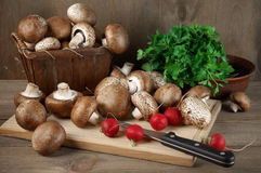Still life with various vegetables. Brown cap mushrooms, radish and parsley with cutting board and knife on rustic wooden background Royalty Free Stock Photos