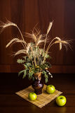 Still life vase and apples. Still life vase with spikelets of wheat and apples Stock Image