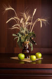 Still life vase and apples. Still life vase with spikelets of wheat and apples Royalty Free Stock Image