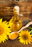 Still life with vegetable oil in a bottle and sunflowers Stock Photo
