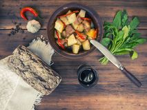 Still life of vegetables, baked potatoes with meat, bread and glass of red wine on the background of wooden table and Royalty Free Stock Images