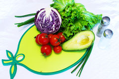 Still life of vegetables and greens on a cutting board. Ingredients for vegetable salad: tomatoes cherry, avocado, lettuce, red cabbage, cucumber on a cutting Royalty Free Stock Photography