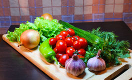 Still life of vegetables and greens on a cutting wooden board. Cherry tomatoes cucumber  chili pepper lettuce onions garlic  parsley and dill Stock Images