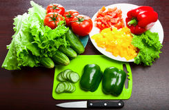 Still life of vegetables. Halved peppers and a knife on a cutting board. Sliced cucumber, tomato, pepper. Lettuce. Vegetables in the dishes Royalty Free Stock Photography
