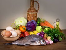 Still life. With vegetables, herbs, eggs, olive oil and fish Stock Image