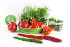 Still life with vegetables at kitchen accessories. Still life with vegetables, knives, a frying pan and spices on a light background Stock Image