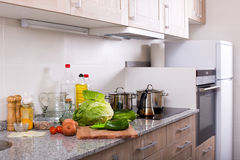 Still life with vegetables in kitchen. Still life with fresh lettuce, pepper and onion in domestic kitchen Royalty Free Stock Photos
