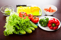 Still life of vegetables. Lettuce with cucumbers, tomatoes, peppers, cutting board and knife on the table. Pieces of chopped vegetables in the bowls Royalty Free Stock Photography