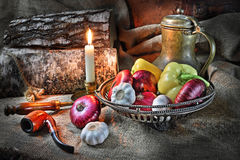 Still life with vegetables in a retro style. Still life in a retro style with a jug, a tube for smoking, red onions, pepper, garlic and a candle against the Royalty Free Stock Photos