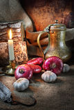 Still life with vegetables in a retro style. Still life in a retro style with red onions, garlic, an ancient jug and a steelyard Royalty Free Stock Image