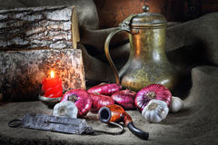 Still life with vegetables in a retro style. Still life in a retro style with red onions, garlic, an ancient jug, a steelyard and a tube for smoking Stock Photos