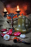 Still life with vegetables in a retro style. Still life in a retro style with red onions, garlic, an ancient jug, a steelyard and a tube for smoking Royalty Free Stock Image