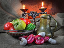 Still life with vegetables in a retro style. Still life in a retro style with red onions, garlic, tomatoes, cucumbers, an ancient jug and a candlestick against Royalty Free Stock Image
