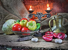 Still life with vegetables in a retro style. Still life in a retro style with red onions, garlic, tomatoes, cucumbers, an ancient jug and a steelyard Royalty Free Stock Images