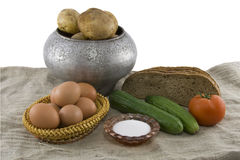 Still-life from vegetarian food. Fresh cucumbers, eggs lying in a wattled small basket, a ripe tomato, fragrant rye bread, a boiled potato in a pig-iron kettle Royalty Free Stock Photography