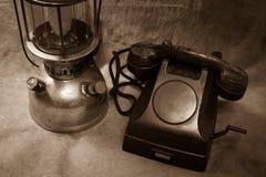 Still life Vintage black phone. Old hurricane lamp sepia tone Royalty Free Stock Images