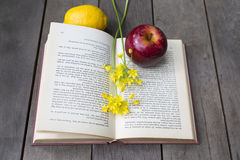 Still life of vintage book with yellow freesia, apple, lemon on Royalty Free Stock Photos