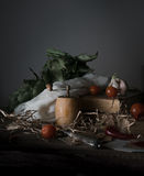 Still life, vintage. cherry tomatoes, laurel, a mill and an old silver knife on  wooden table. Stock Photo