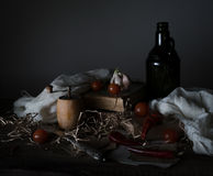 Still life, vintage. cherry tomatoes, old bottle with the oil mill and the  silver knife on a wooden table. Stock Photography