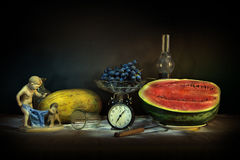 Still life with vintage objects, melon and watermelon. Dark still life shot the light brush. On the table are vintage statuette, a kerosene lamp, a clock, a vase Royalty Free Stock Photos