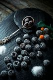 Still life in style. Close up frozen berry of blackberry with spoon and sugar on black stone stand. Still life in vintage style. Close up frozen berry of stock photos