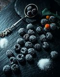 Still life in style. Frozen berry of blackberry with spoon and sugar on black stone stand. Still life in vintage style. Frozen berry of blackberry with spoon and stock photography
