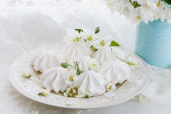 Still life in vintage style with meringue kisses and cherry flowers on rusted wooden table Stock Photo