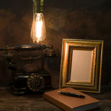Still life of vintage telephone with picture frame and diary on Royalty Free Stock Photo