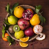 Still life fruit basket. flavors and colors. Still life with vintage wooden plate full of citrus fruits and fresh mixed fruit Stock Photos