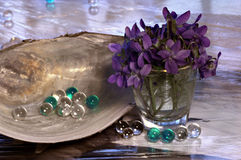 Still life with violets. A beautiful still life with violets, glass beads and shell. An interesting background and dense saturated and vivid colors royalty free stock photography