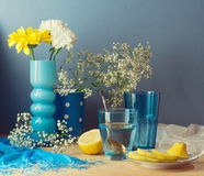 Still life with water, lemon and flowers on wooden table Stock Images