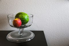 Still life watermelon and apple in a crystal bowl on a table. A crystal bowl on a brown table with a watermelon and apple Royalty Free Stock Photos