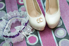 Still life with wedding bride shoes and garter and gold rings Royalty Free Stock Photo