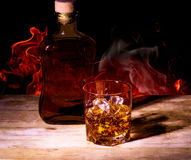 Still Life with Whiskey. On the background of fire Stock Photos