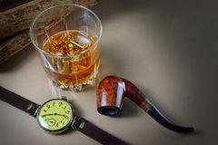 Still life with a whisky glass and a tube for smoking in a retro royalty free stock photos