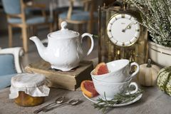 Still life. White beautiful teapot, cups and saucer, apricot jam, grapefruit and rosemary. royalty free stock photography