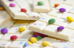 Still life of white chocolate with smarties. Inside, indoor, indoors, interior, interiors, food, nutritive, nutrition, nourishment, chocolates, bar, bars royalty free stock image